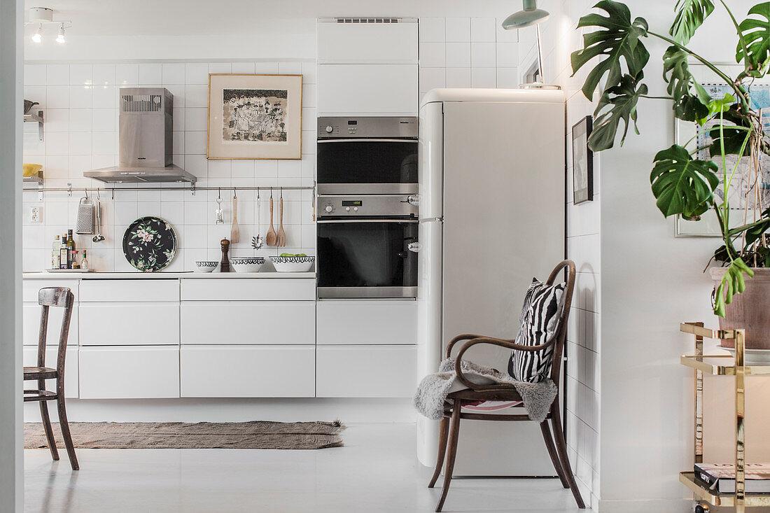 Große weiße Wohnküche mit Vintage-Deko