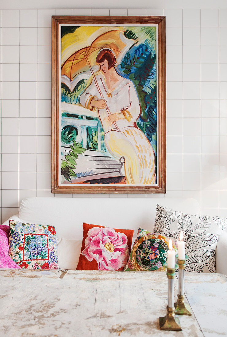Colourful scatter cushions on sofa below painting on tiled wall