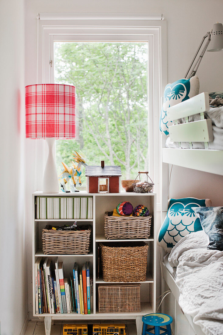 Baskets and books on shelves next to bunk beds in children's room