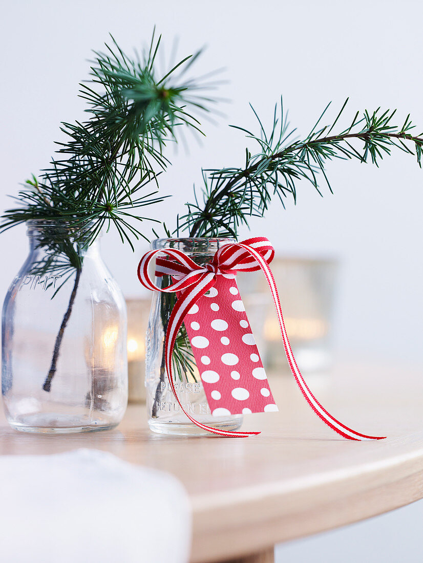 Coniferous branches in glass vases decorated with a ribbon and cards