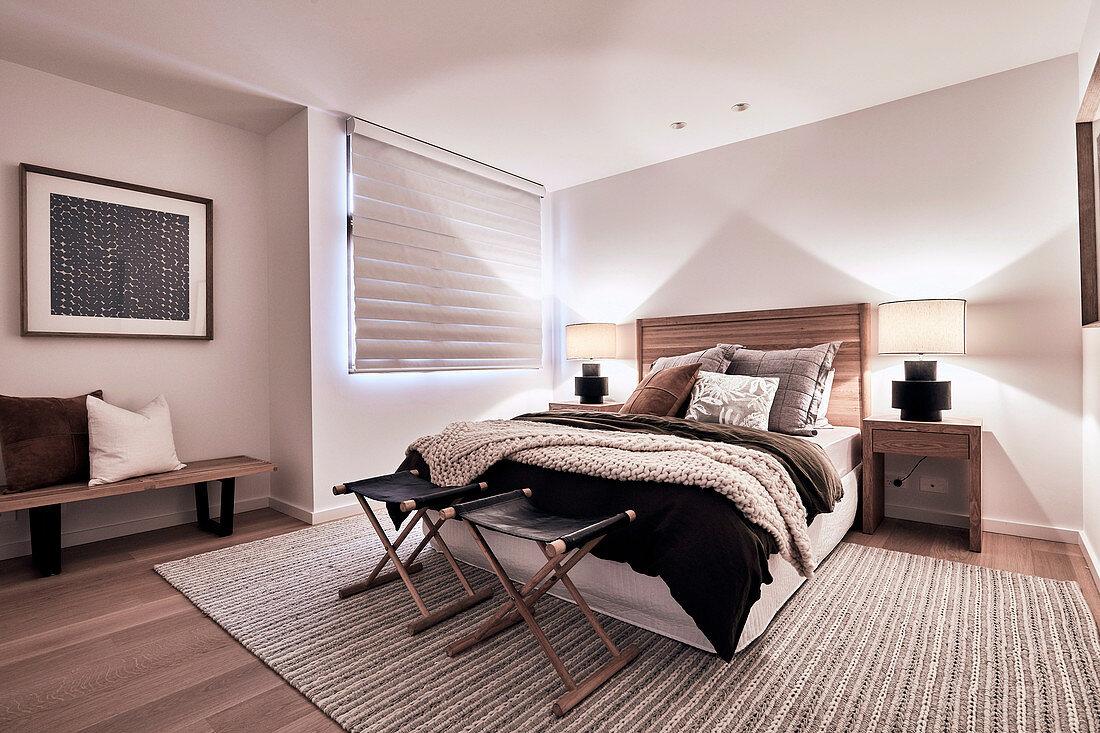Abgedunkeltes Schlafzimmer in Brauntönen mit Beleuchtung