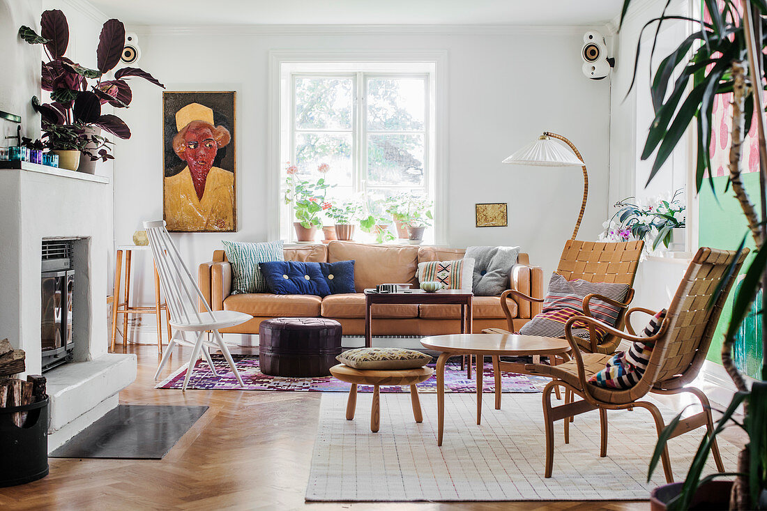 Various seating, tables, houseplants and fireplace in living room