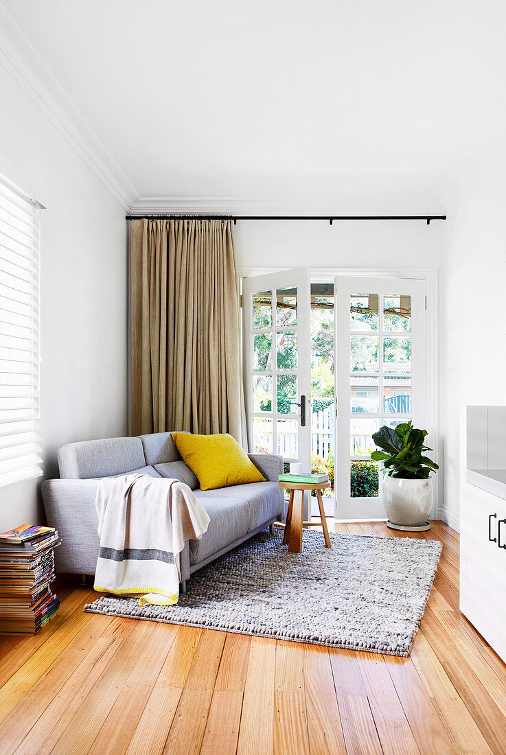 Upholstered sofa, side table and houseplant in the room with terrace access