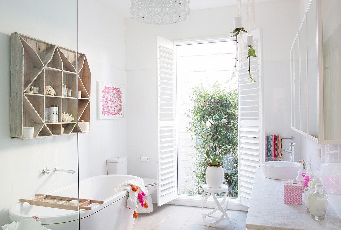 Shelf over bathtub, toilet, open shutters and vanity in bright bathroom