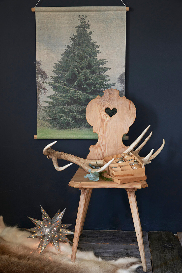 Antlers and Christmas baubles on farmhouse chair below picture of tree
