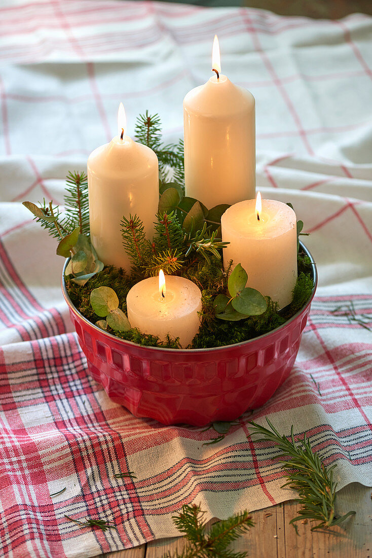 Four white candles and leafy twigs in bundt-cake tin