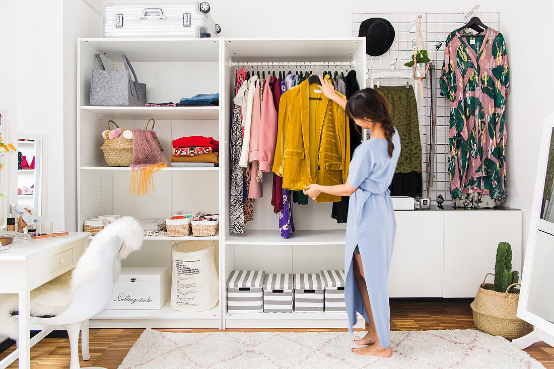 Woman in dressing room with open-fronted wardrobes