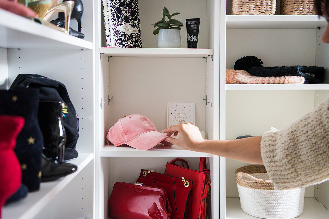 Women's accessories on open shelves in dressing room; hand picking up cap