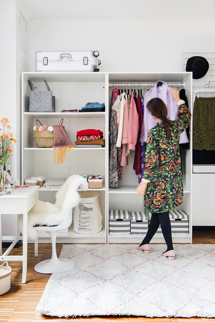 Woman standing in front of open wardrobe in dressing room