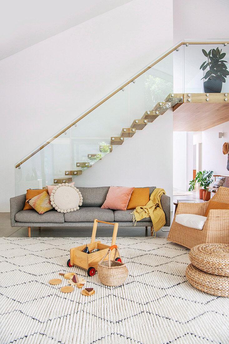 Graues Sofa vor freitragender Treppe im antroposophischen Wohnzimmer