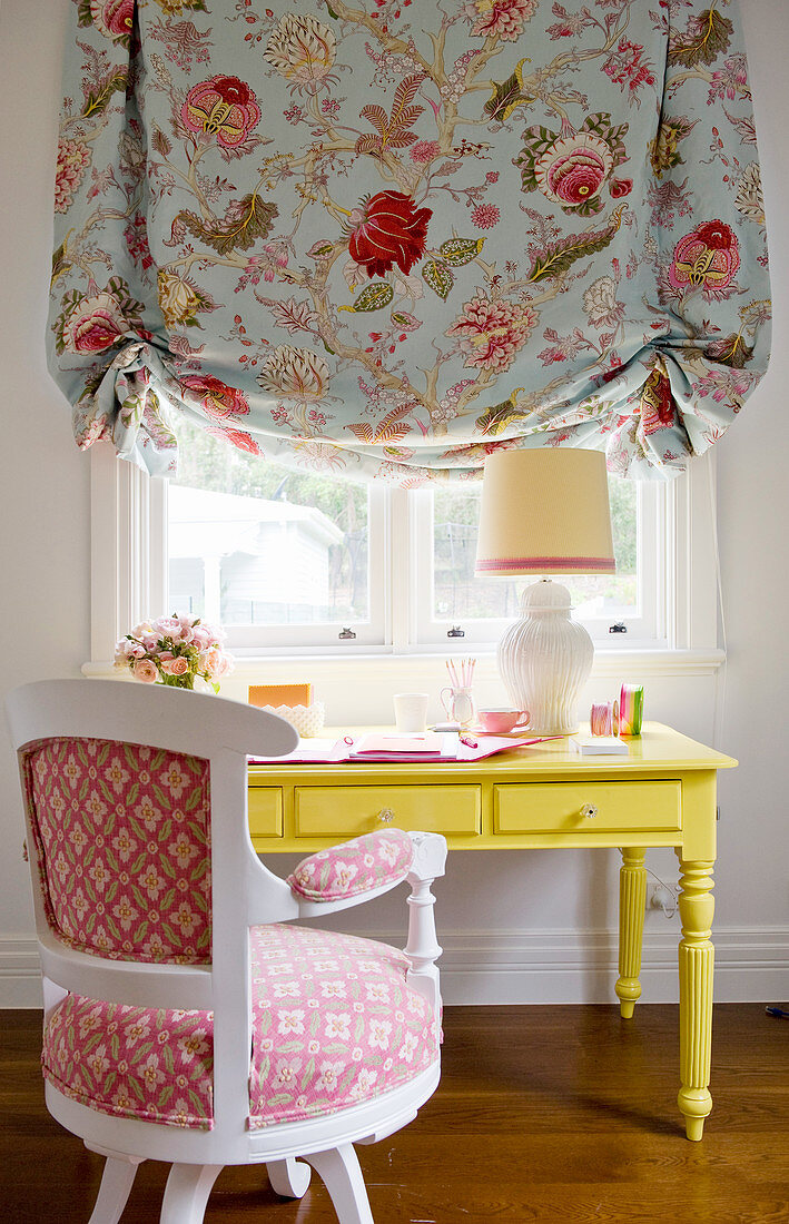 Yellow desk below window with floral Roman blind