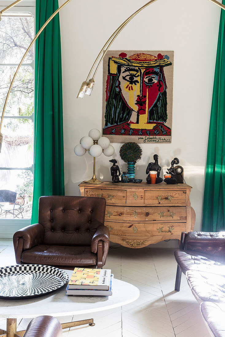 Painting above wooden chest of drawers, coffee table and leather armchair in living room