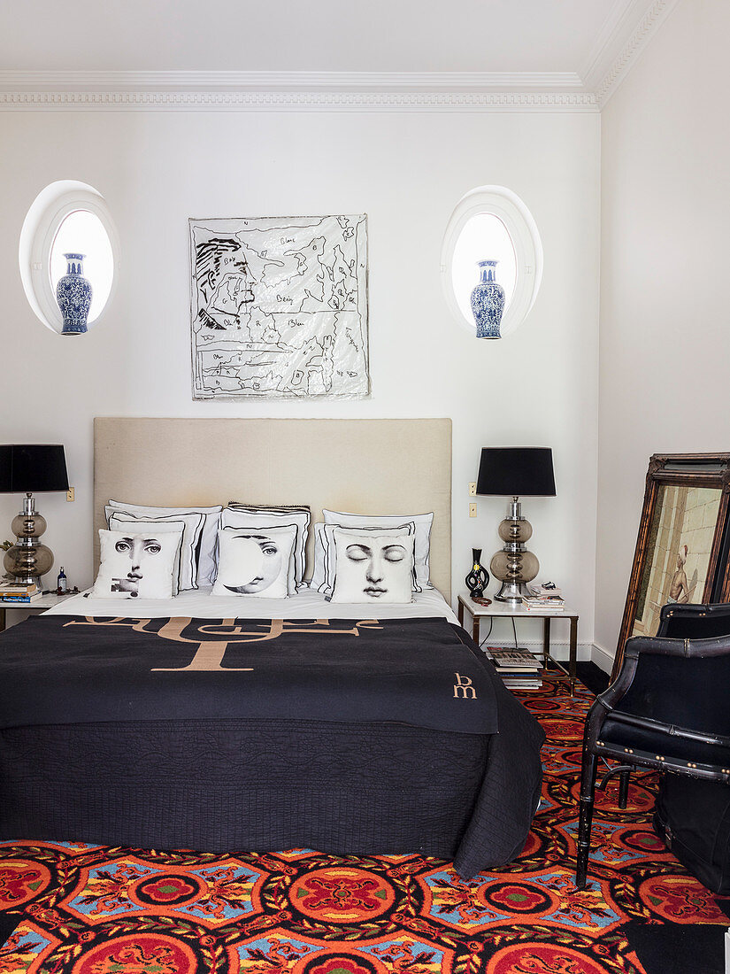 Double bed with designer scatter cushions and dark bedspread in bedroom and colourful patterned rug on floor