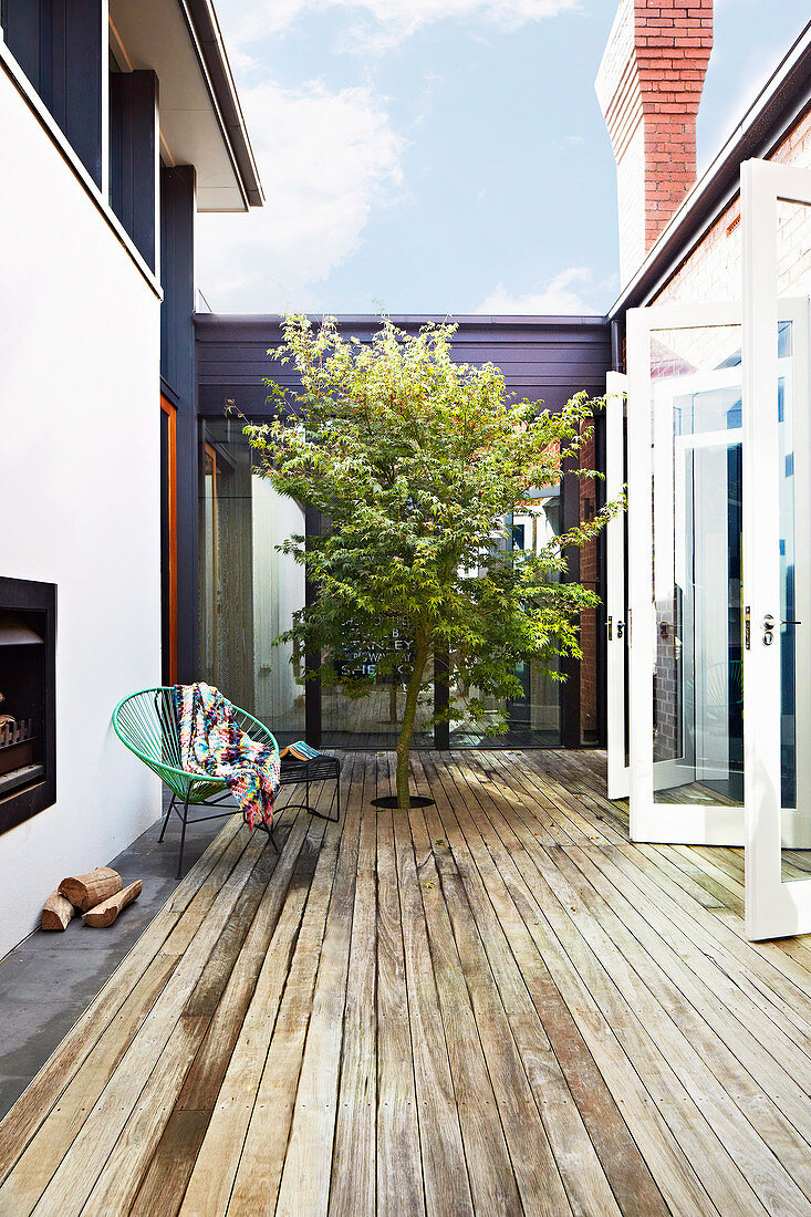 Chair on wooden terrace with integrated tree