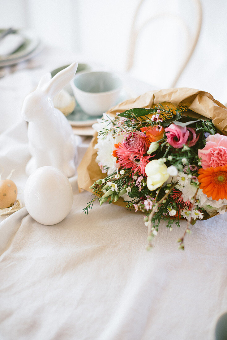 Colourful spring bouquet wrapped in paper on table set for Easter