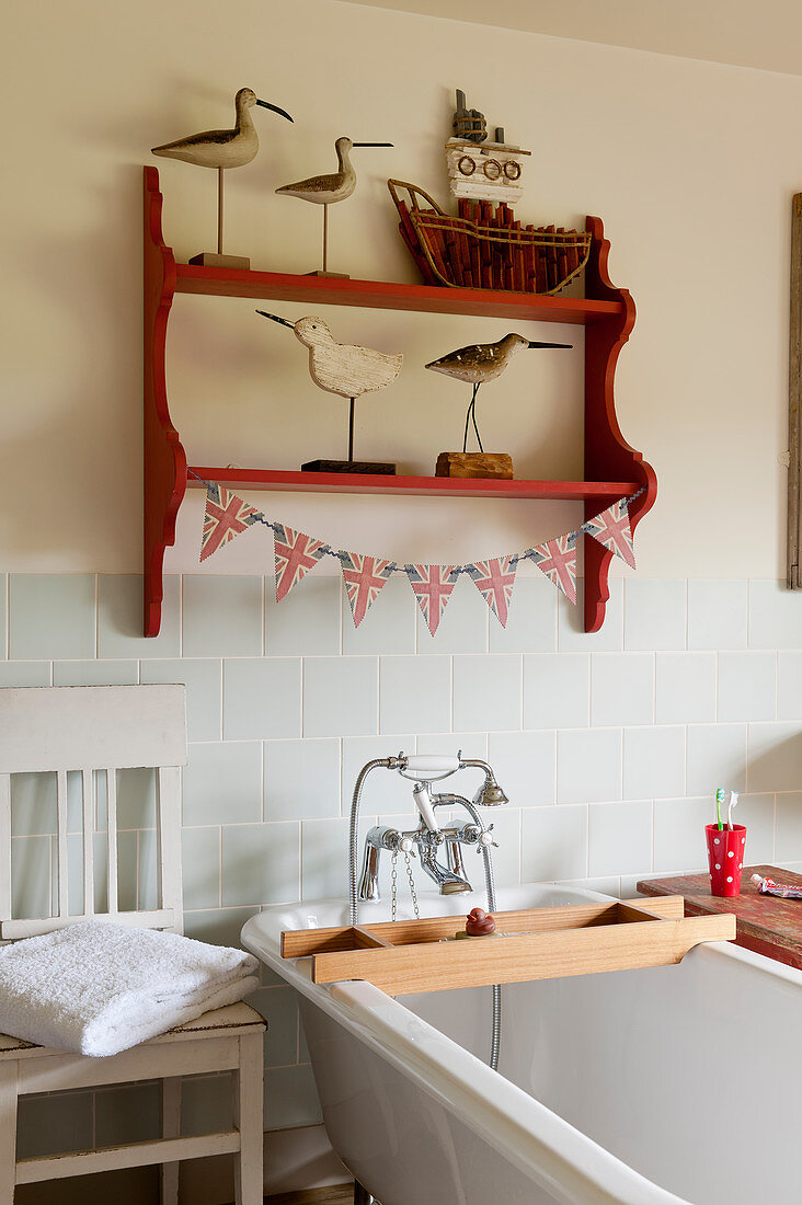 Wooden bird statues on red shelf in bathroom with decorative union jack bunting