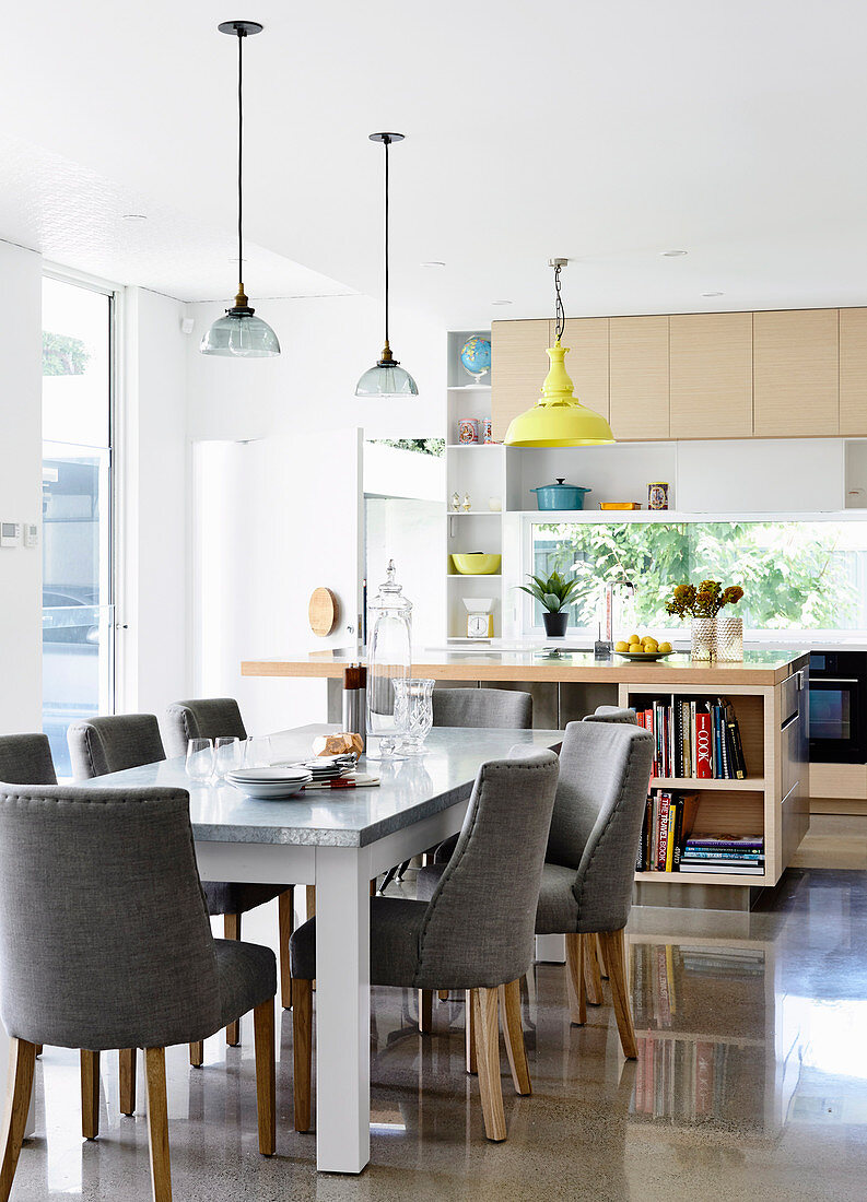 Dining area with gray upholstered chairs in a bright, open kitchen with counter and polished concrete floor