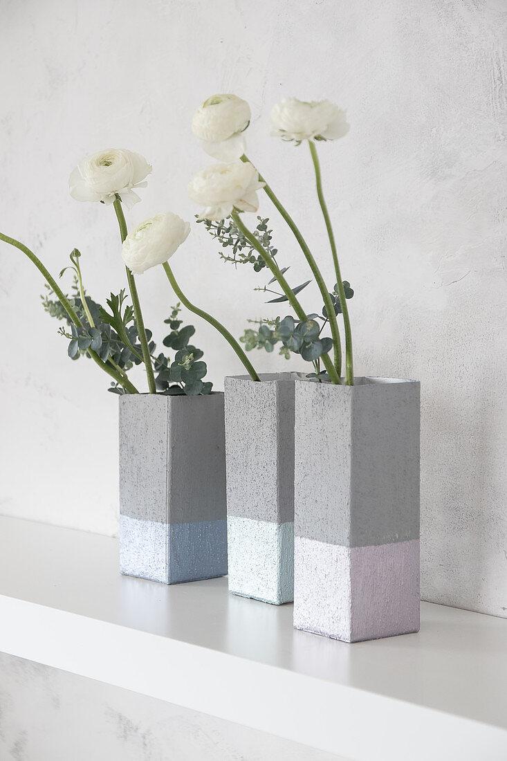 Concrete-effect vases handmade from milk cartons holding ranunculus on shelf