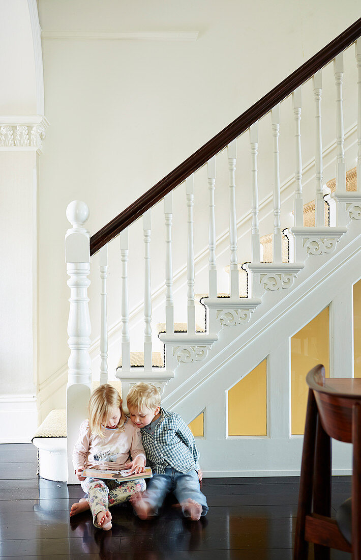 Elegant staircase with white stairs and dark wooden floor, children reading on the floor