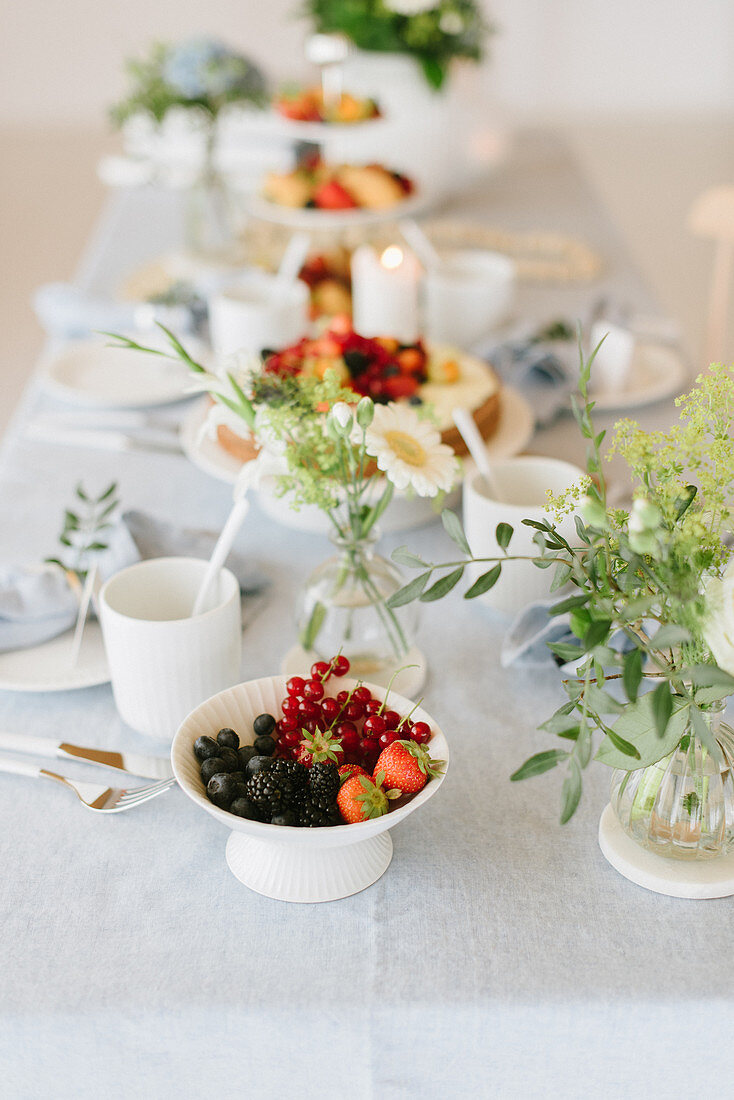 Bowl of berries and cape gooseberries on table festively set for afternoon coffee