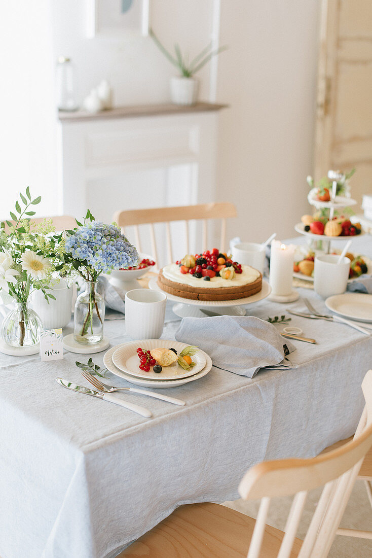Cakes and flowers on table festively set for afternoon coffee