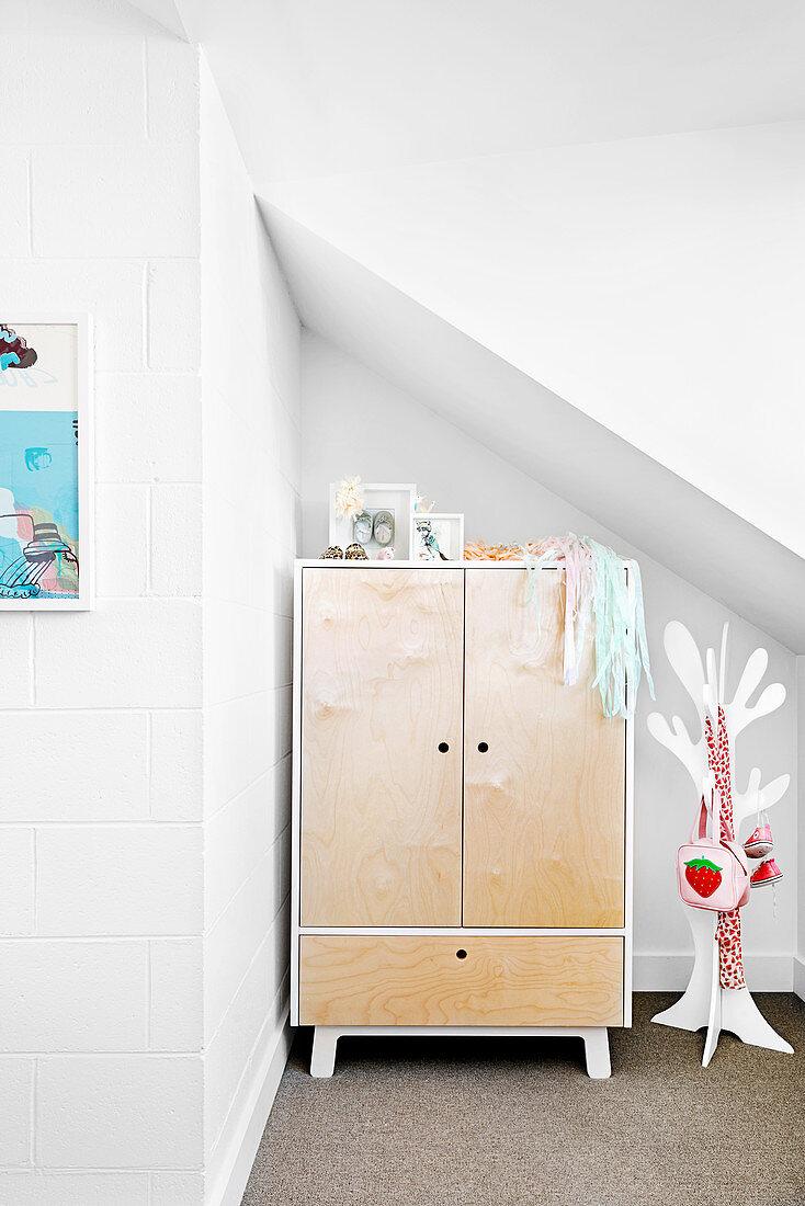 Wardrobe and coat rack in tree shape under sloping ceilings in white children's room