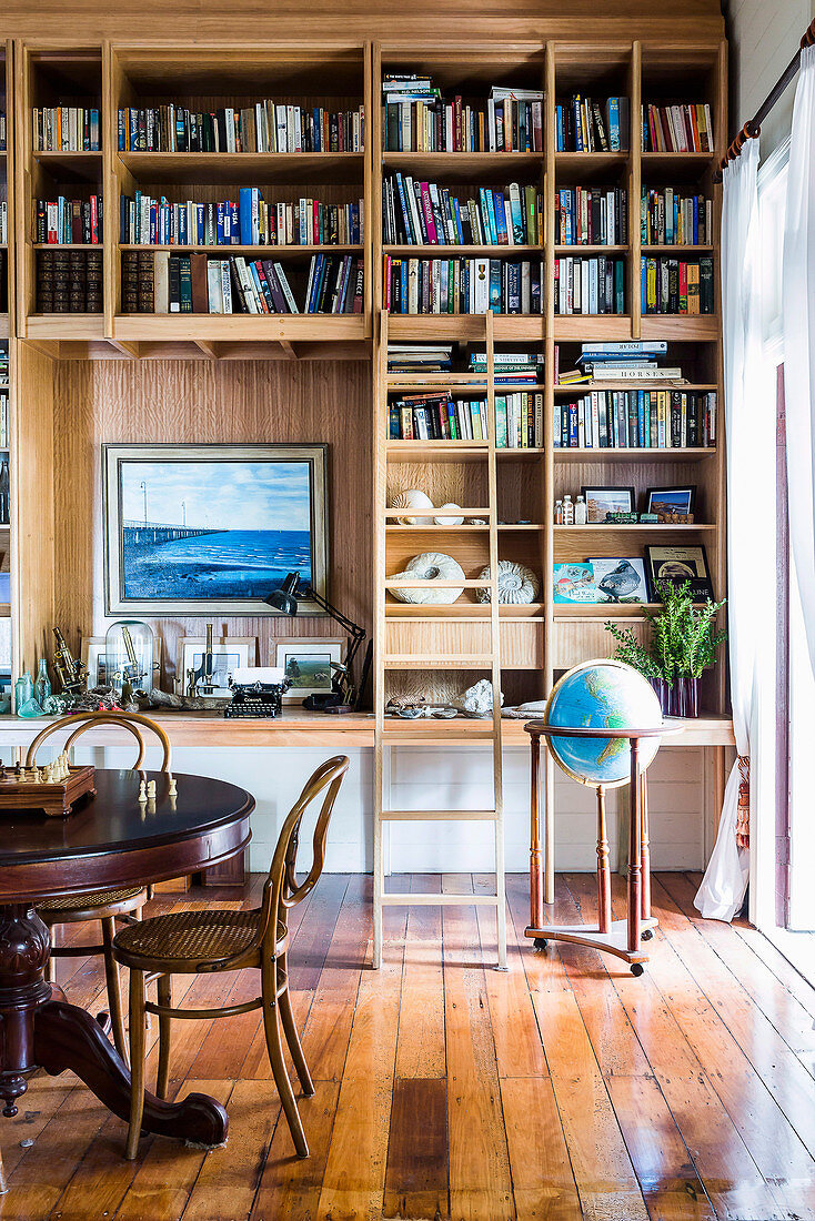 Bookshelf with library manager, globe and round table with chess in the study