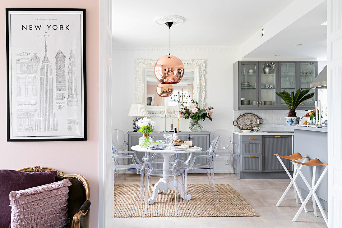Open-plan kitchen with pale grey cupboards, round dining table and designer chairs with antique armchair and poster of New York in foreground