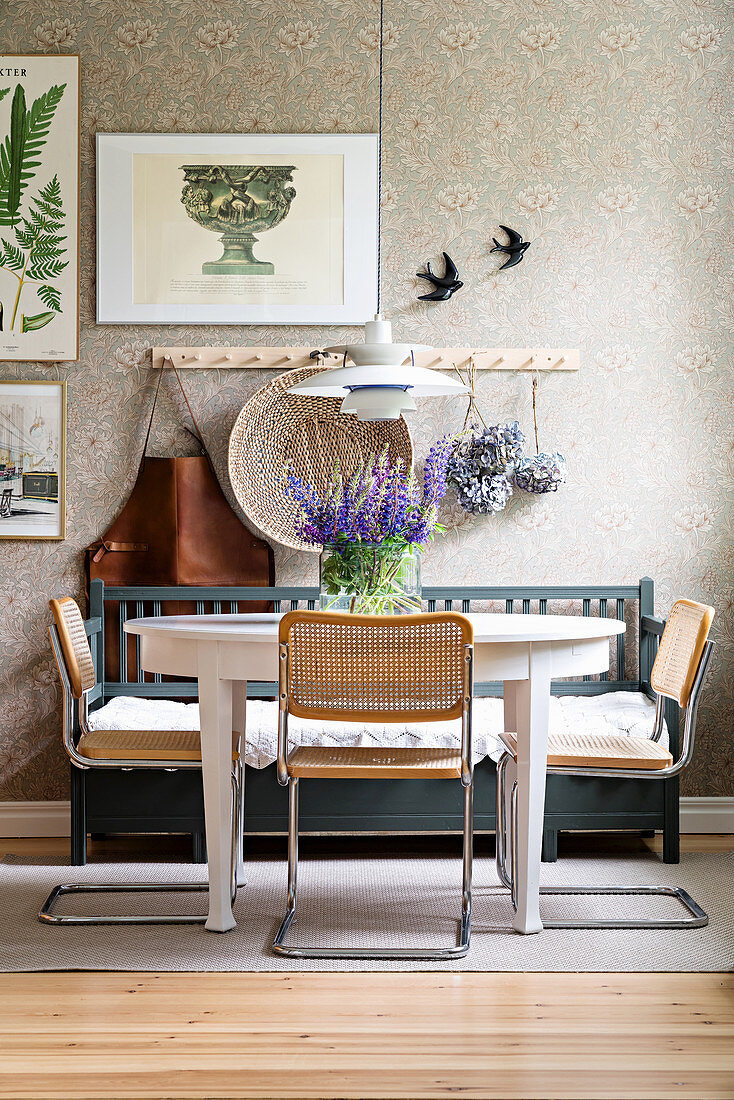 Cantilever chairs with cane seats and backrests at dining table with rustic wooden bench