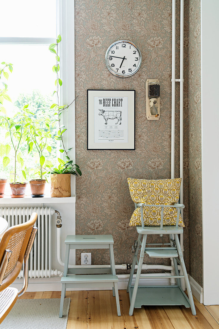 Blue-grey high chair and stool against vintage wallpaper