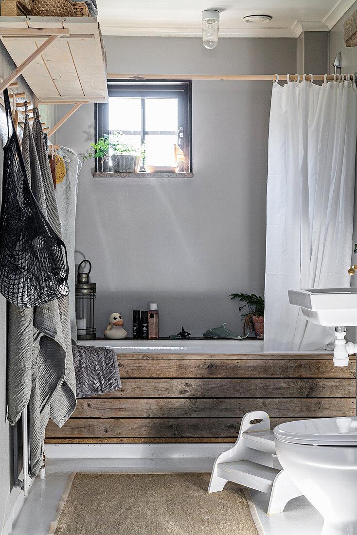 Bathtub clad with rustic boards against grey wall