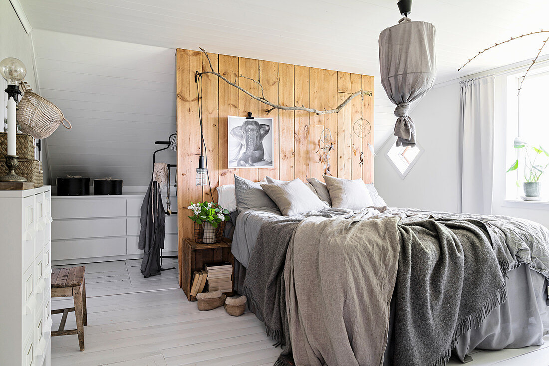 Bed against board wall used as partition in bedroom