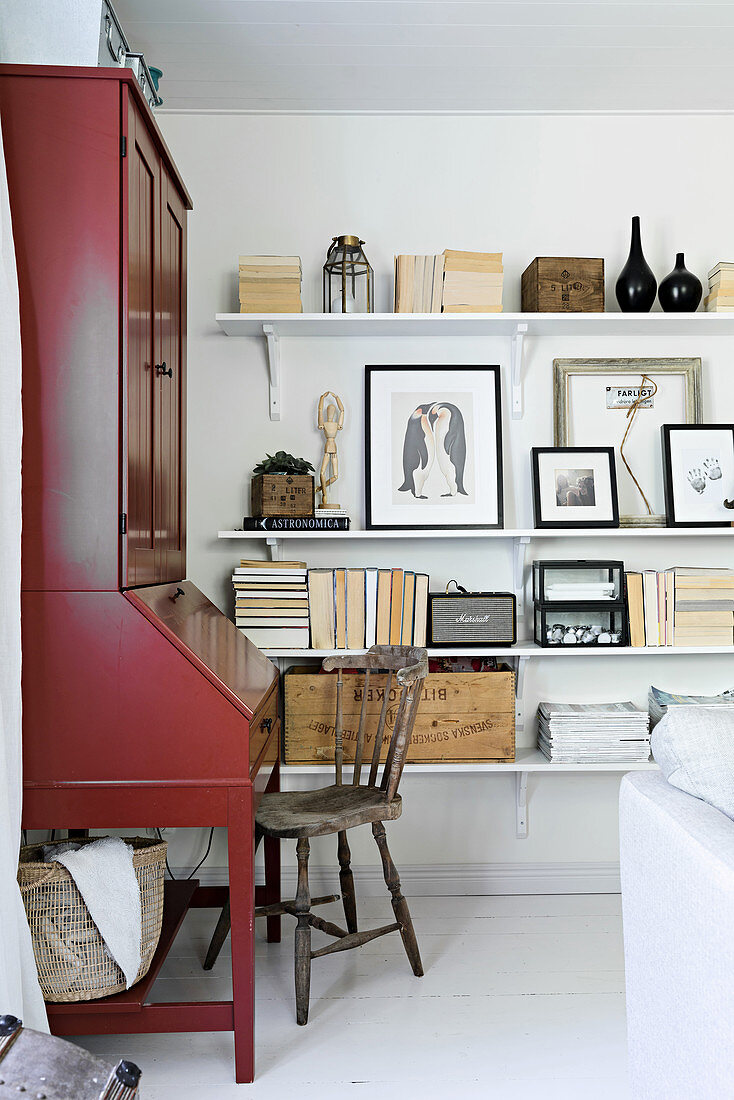 Red bureau next to shelves decorated with ornaments in natural shades