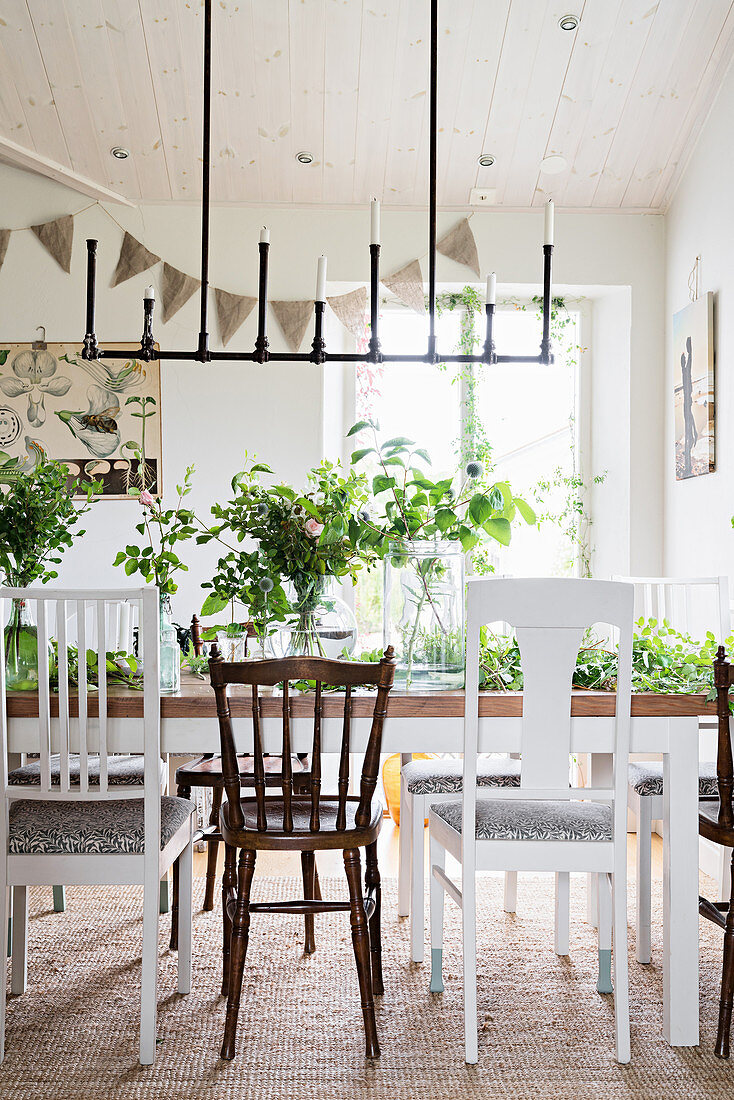 Simple candle chandelier above dining table and various chairs