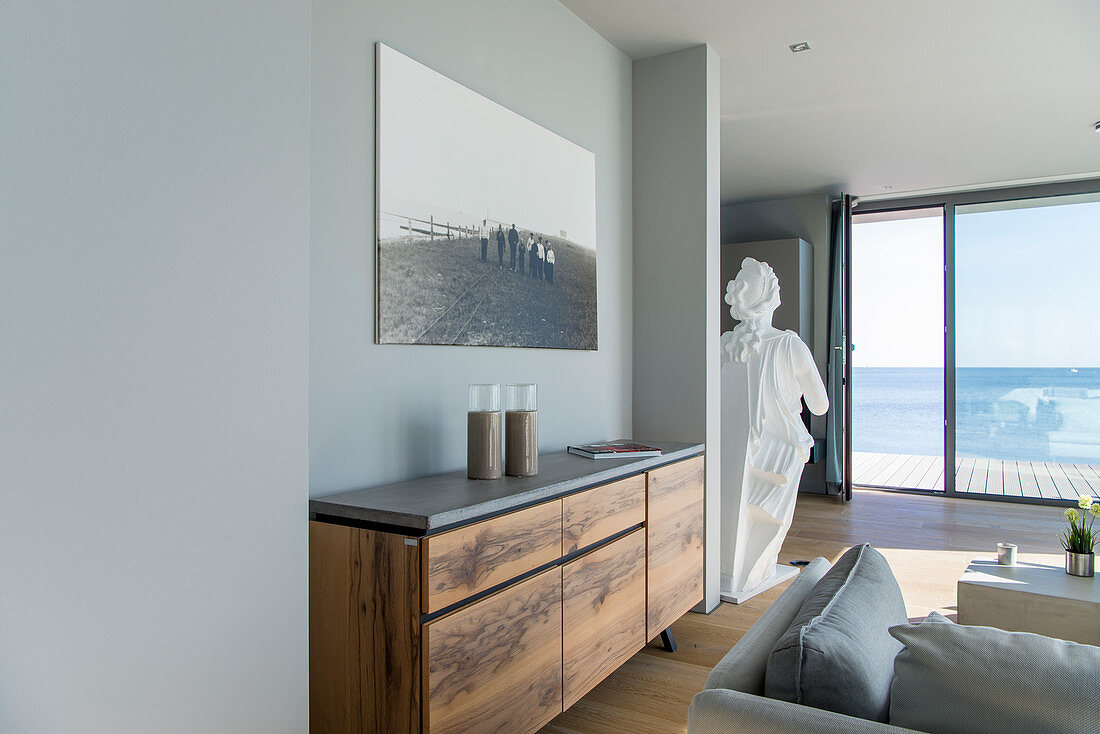White ship's figurehead as monumental decorative piece in interior with sea view
