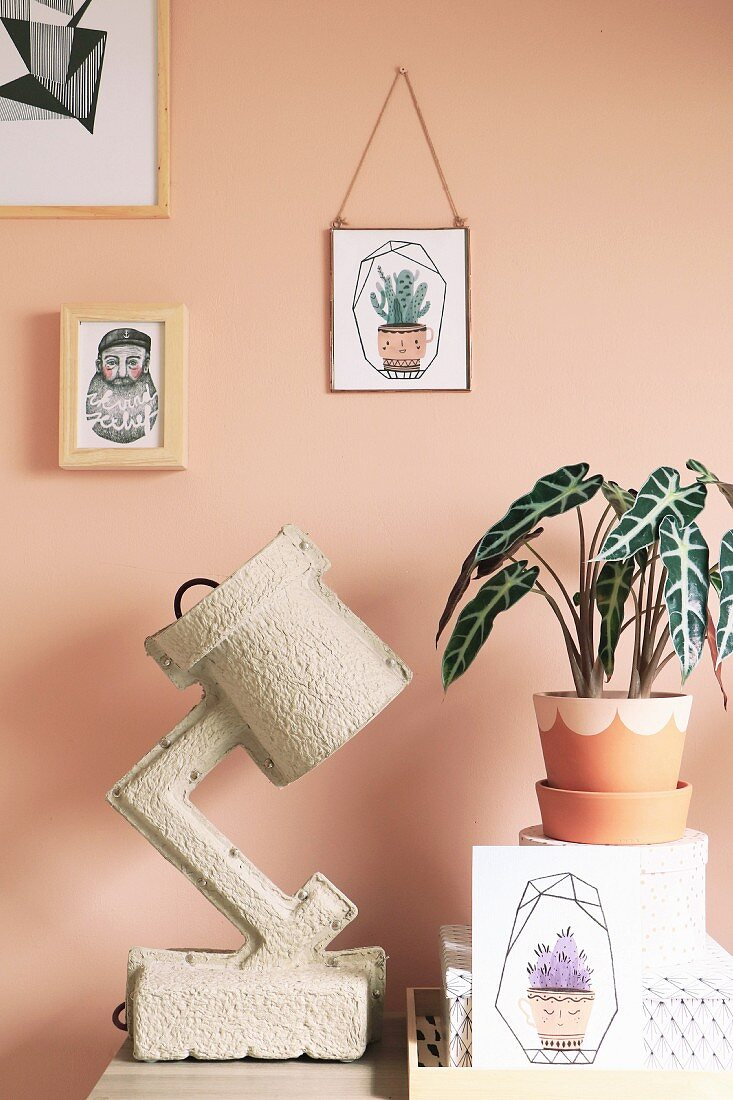 Elephant ear in painted terracotta pot next to paper lamp