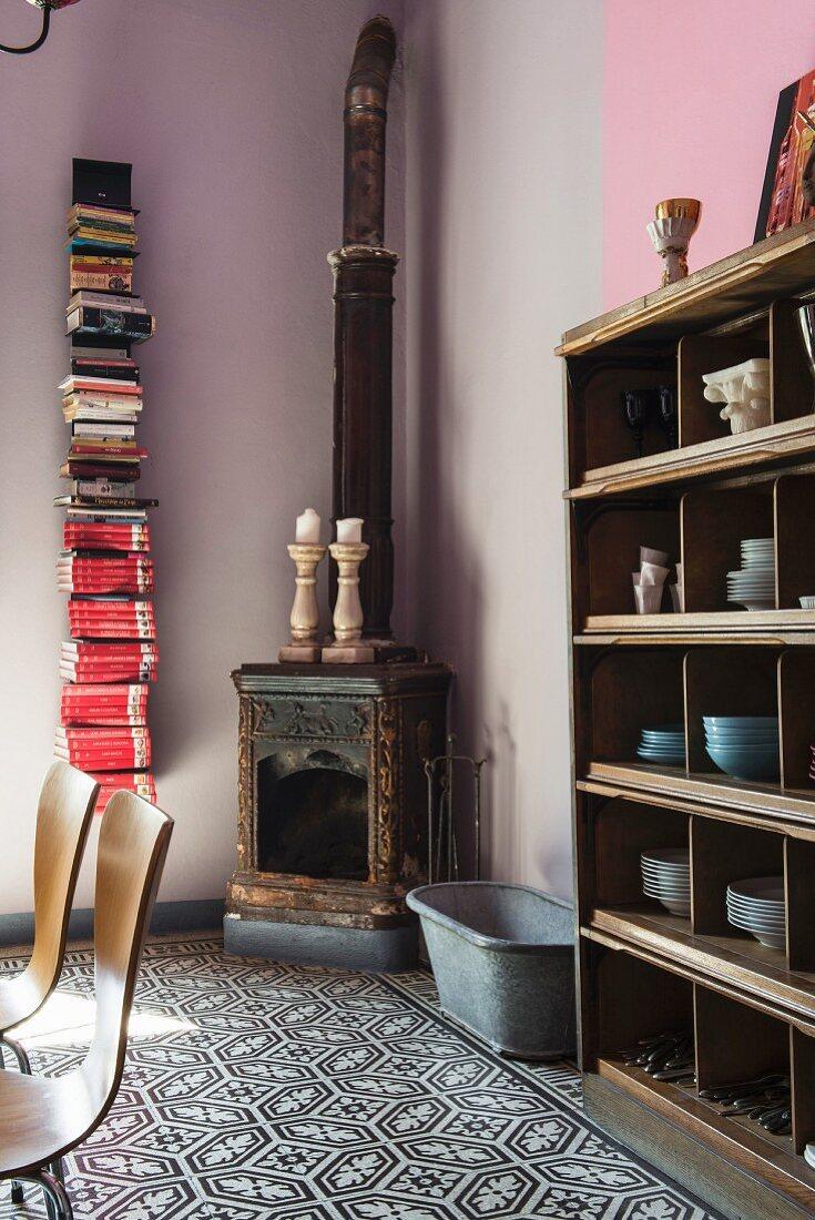 Old wood-burner in corner next to vertical bookshelf