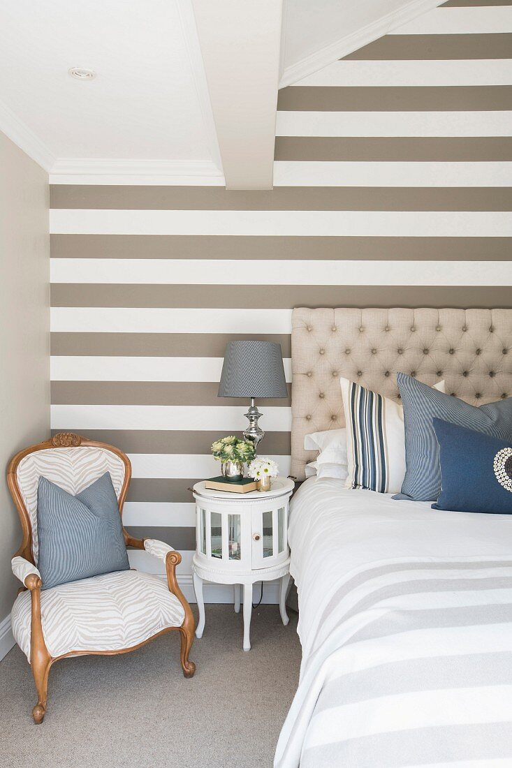 Striped accent wall in elegant bedroom in shades of beige, white and blue