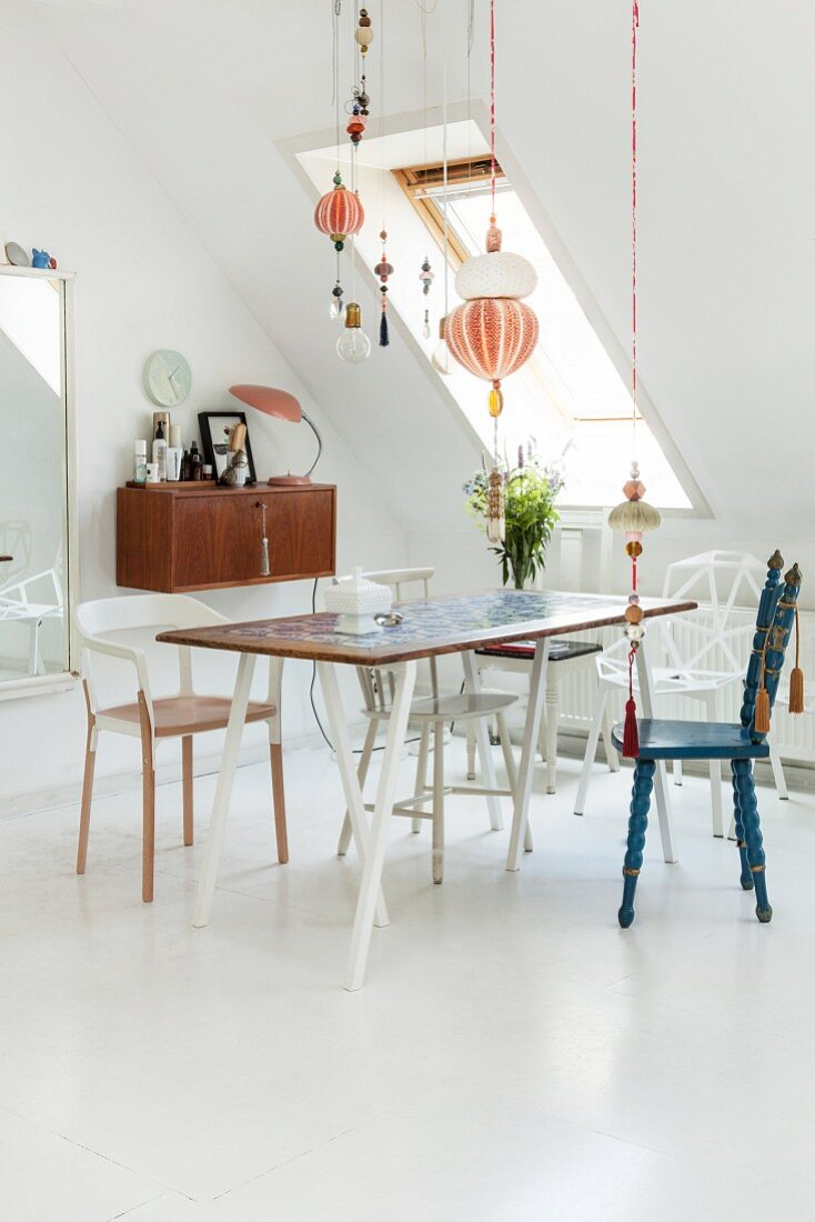 Dining table, various chairs and pretty suspended ornaments