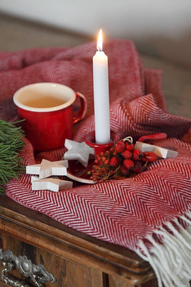 Advent arrangement of rose hips, white wooden stars and lit candle