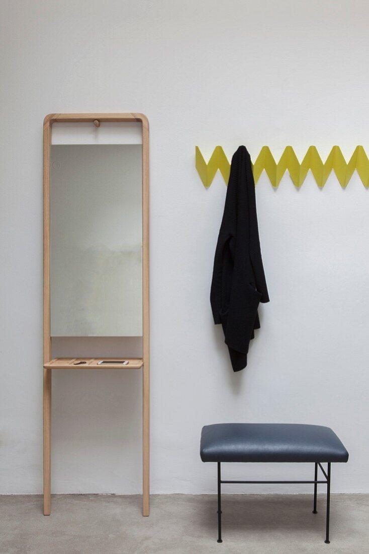 Gelbe Zickzack-Wandgarderobe neben schlichtem Standspiegel mit Ablagefläche und Hocker