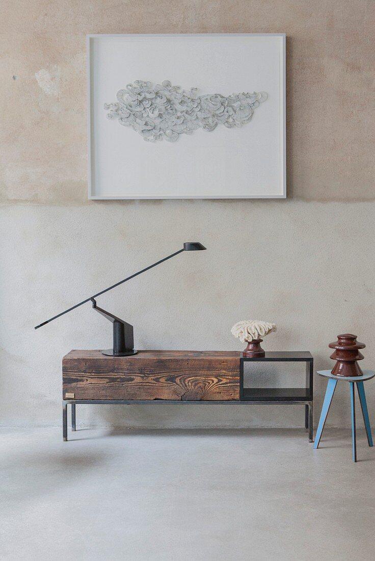 Black table lamp on simple low sideboard made from reclaimed wood below framed artwork