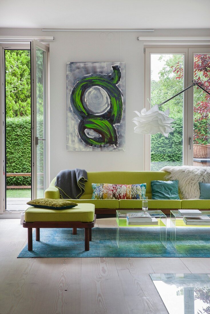 Green sofa on blue rug in front of floor-to-ceiling windows