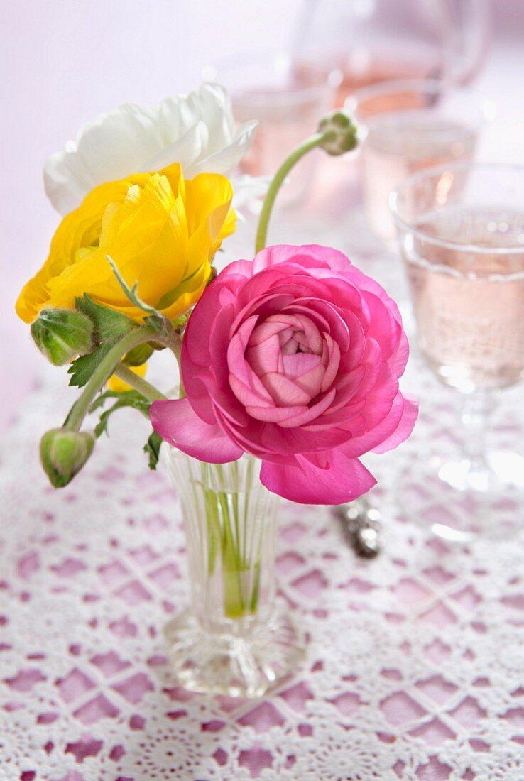 Rosafarbene, gelbe und weisse Ranunkeln in Vase auf Häkeldecke