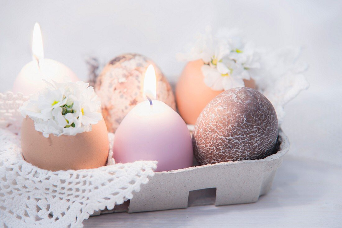 Lit candles and eggs in egg box decorated with white flowers and crocheted doily
