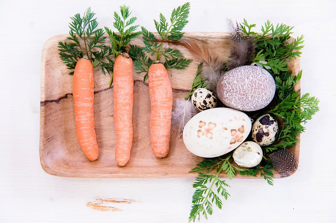 Carrots, carrot leaves, feathers and various decorated eggs in wooden dish