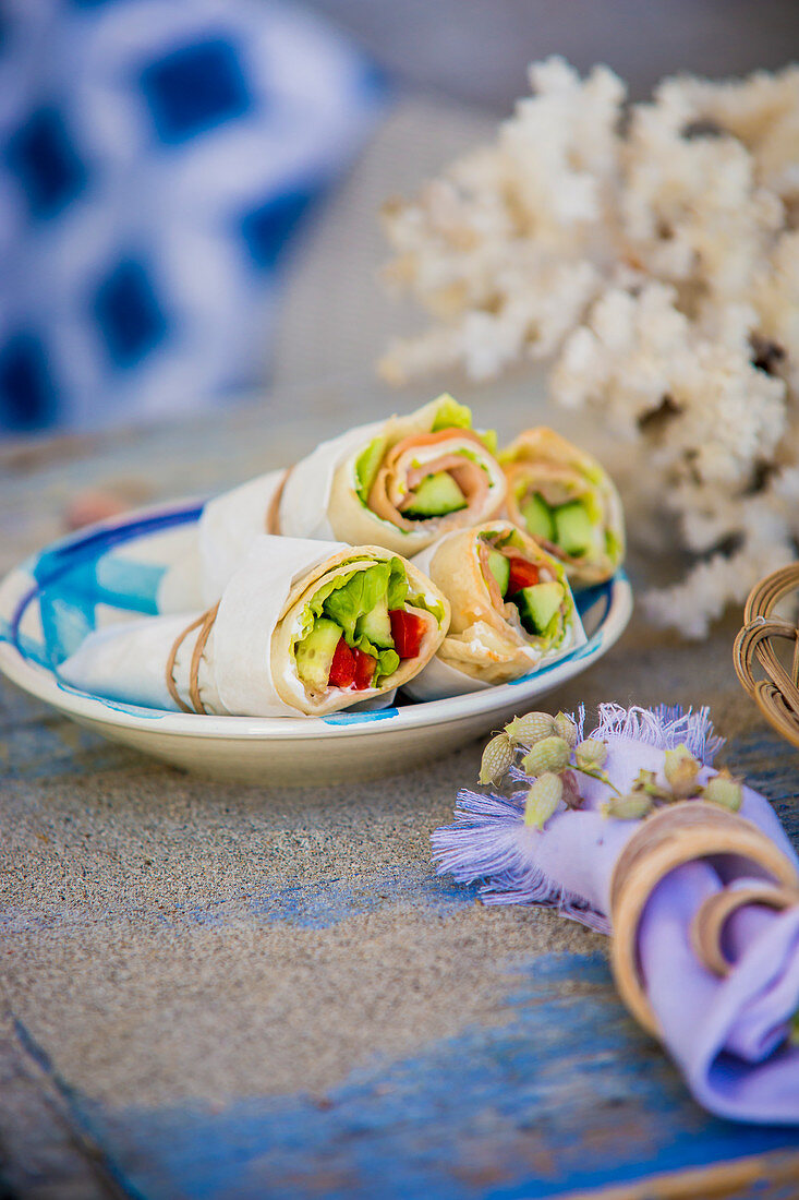 Wraps in parchment paper on plate on table set in Mediterranean style