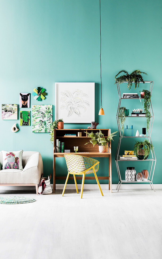 Secretary with armchair, open shelf with house plants and sofa against green wall