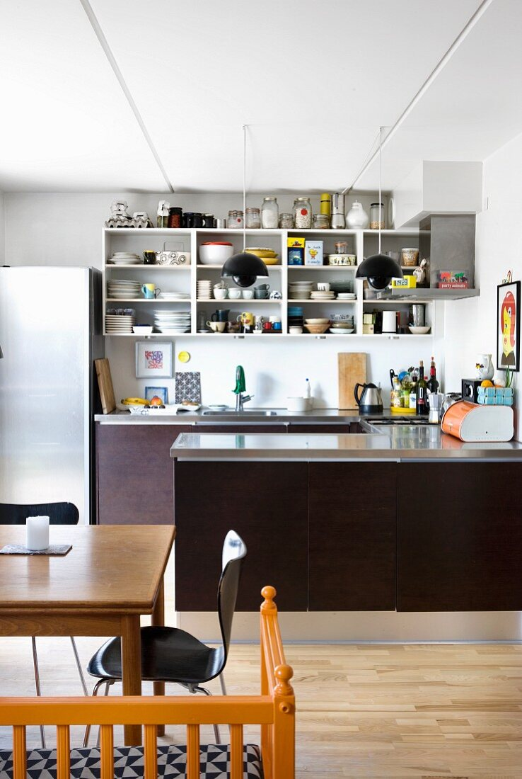 Open-fronted shelves and U-shaped base units in kitchen with dining area in foreground