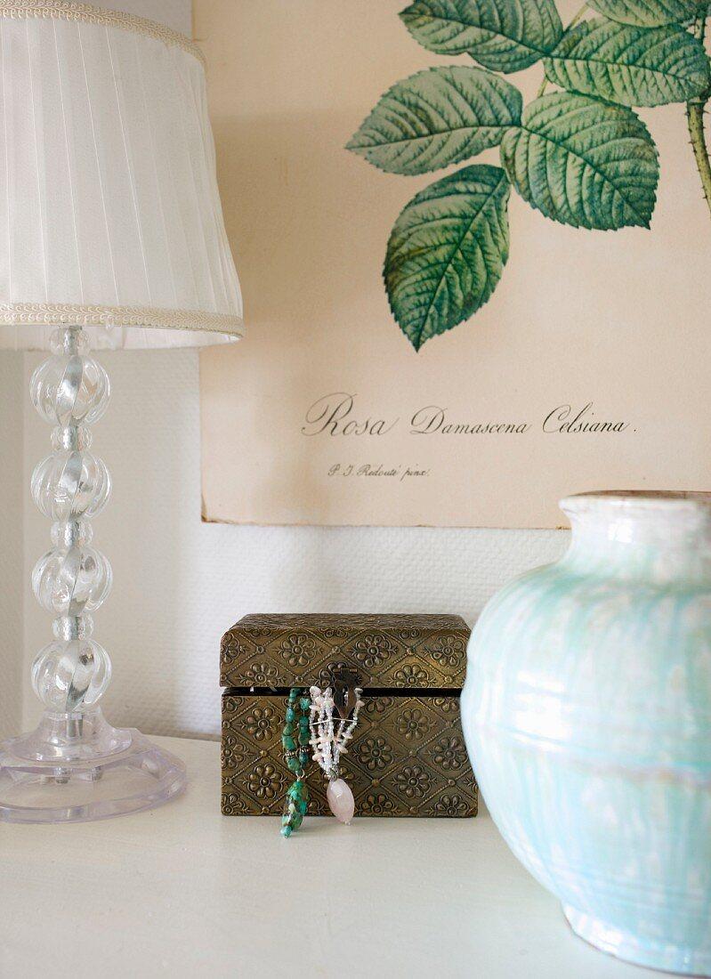 Vase, lamp and jewellery box below botanical illustration on poster